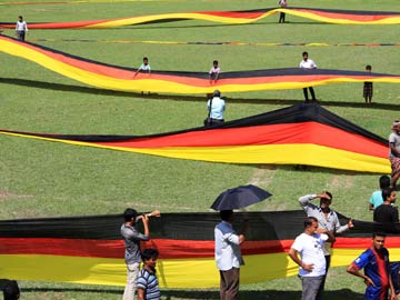 In this photograph taken on July 12, 2014 and released by the German Embassy in Dhaka, Bangladeshi residents stand alongside a large German flag displayed at a stadium in Magura.